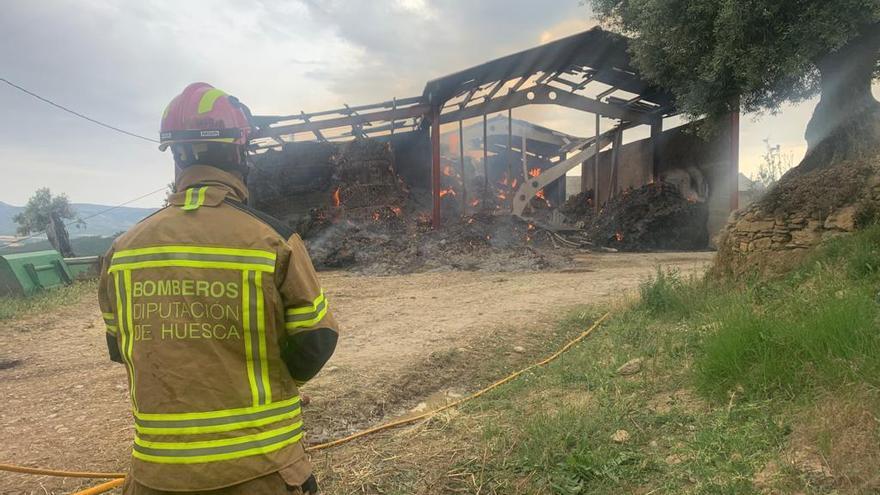 Los bomberos de la Diputación de Huesca sofocan un incendio en una nave llena de paja en Güel