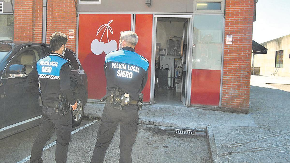 Dos agentes de la Policía Local ante el local del conflicto por ruidos en La Fresneda.