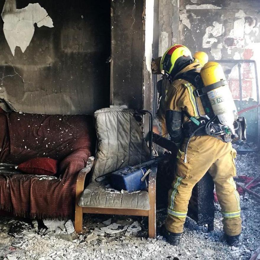 Un bombero en la casa incendiada.