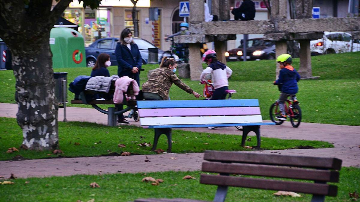 """Niños, ayer, jugando en los Xardíns do Concello junto al banco del """"Orgullo Trans"""".     // G. NÚÑEZ"""