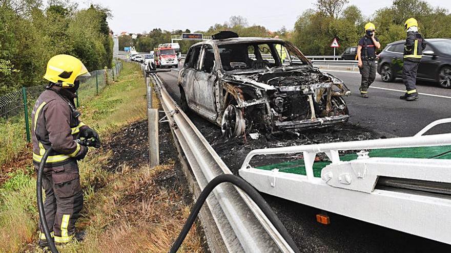 Bomberos apagan un coche en llamas en la autopista
