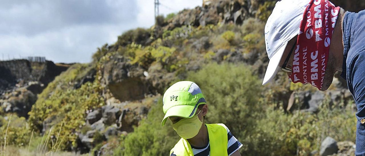 Javier Littler, de seis años, recoge basura del barranco de Telde con su padre. | | ANDRÉS CRUZ