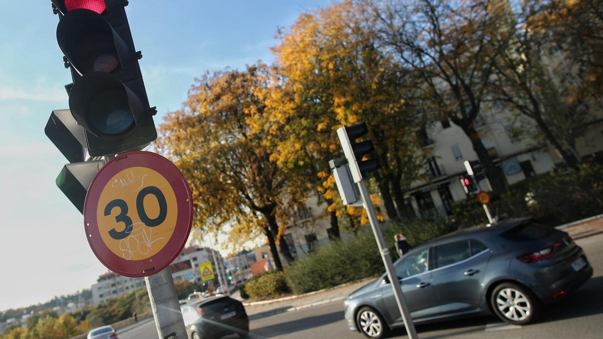 Varios coches circulan al lado de una señal de tráfico.
