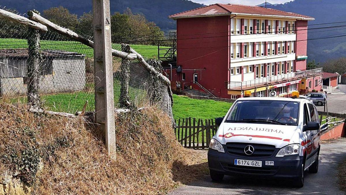 Una ambulancia, trasladando al hospital a uno de los residentes del centro Abuli, al fondo de la imagen, al mediodía de ayer.