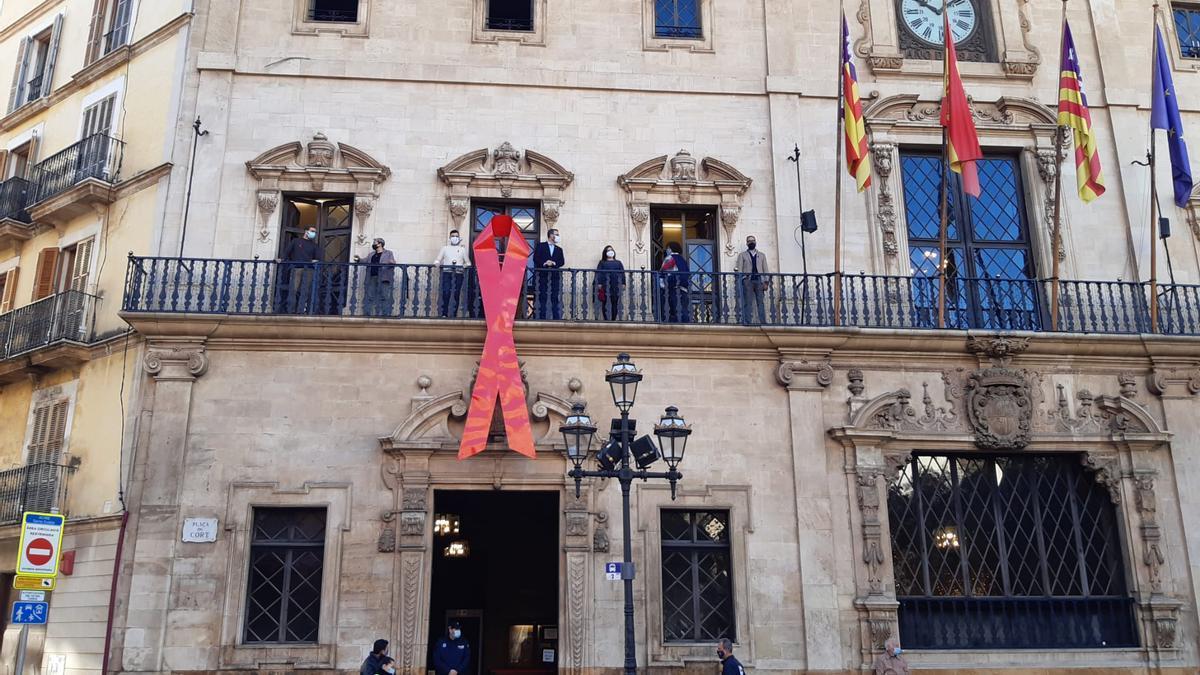 Colocación del lazo rojo de la lucha contra el SIDA en el balcón de Cort.