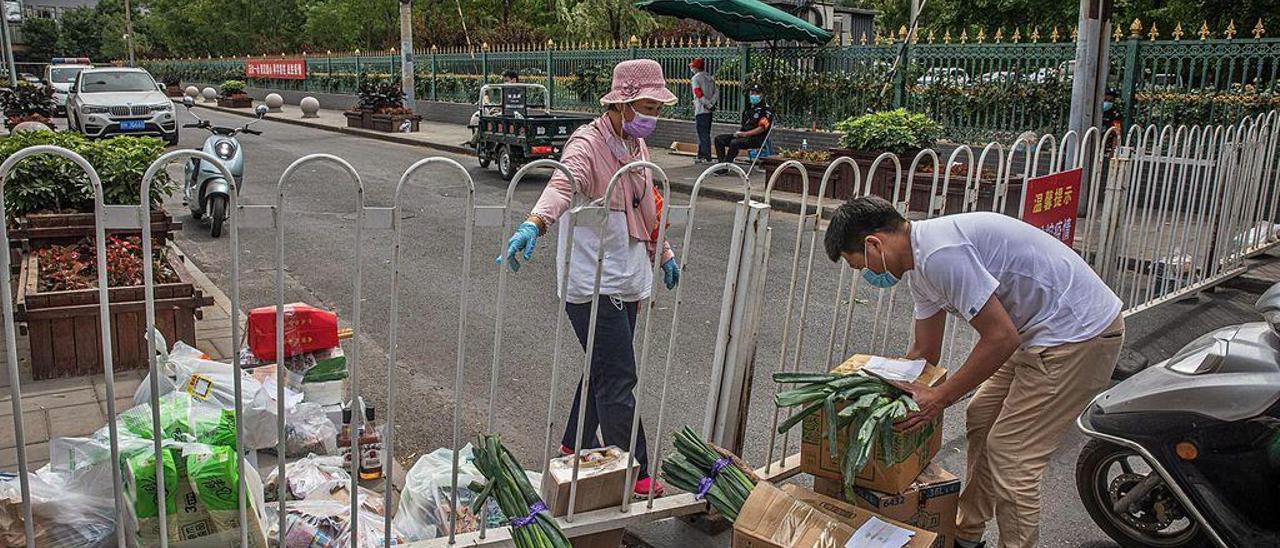 Un hombre lleva cajas de alimentos hasta la valla que delimita una zona confinada de Pekín.
