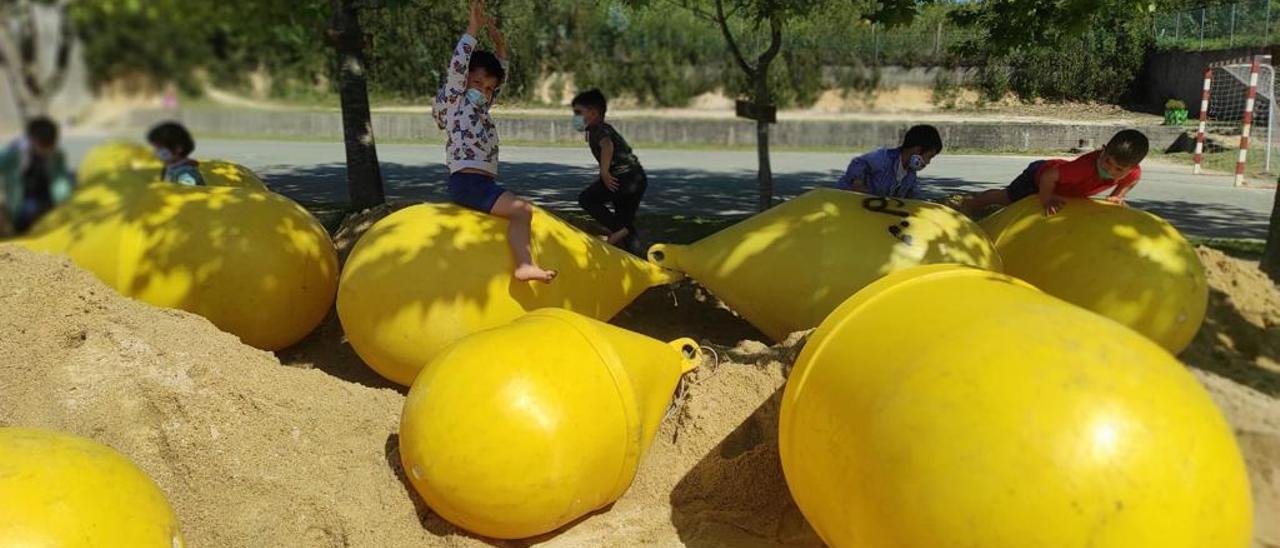 Alumnos del CEIP Carlos Casares de Vilariño disfrutan de las boyas en el patio.