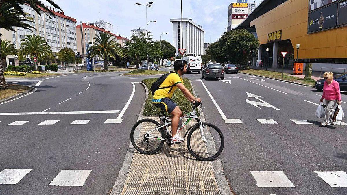 Un ciclista y una peatón en la avenida Salvador de Madariaga, en el barrio de Elviña.