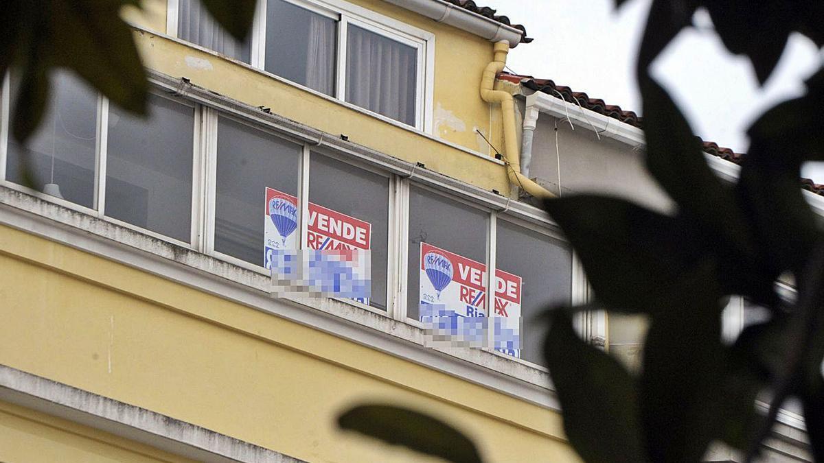 Carteles en las ventanas de un piso en venta. |   // VÍCTOR ECHAVE