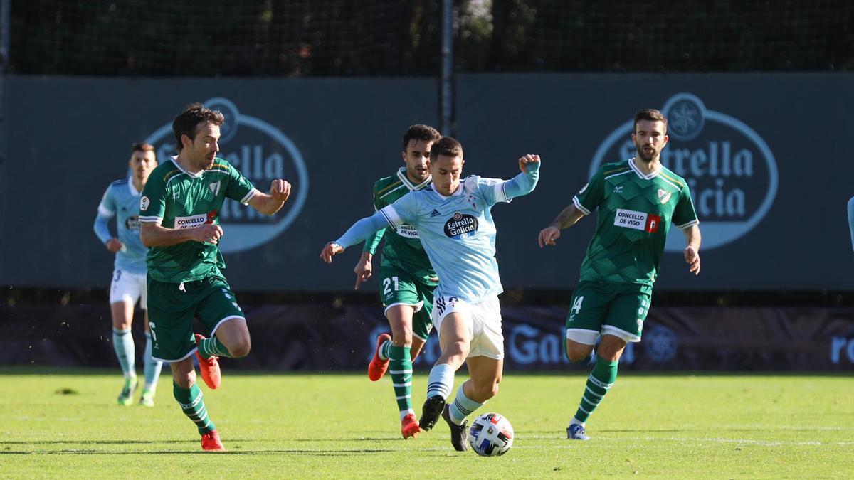 Manu Justo controla un balón perseguido por varios jugadores del Coruxo.