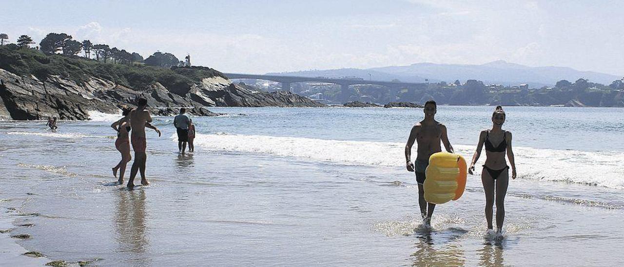 Bañistas hace unos días en la playa de Arnao, en la bocana de la ría del Eo, con Ribadeo al fondo.