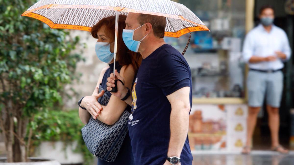 Una pareja pasea hoy por València con mascarilla y paraguas.