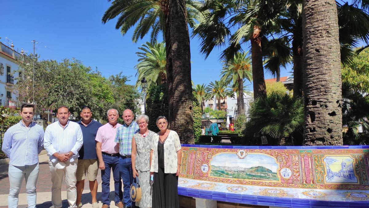 La alcaldesa, junto a los artistas, la empresa constructora y concejales, al lado del banco.
