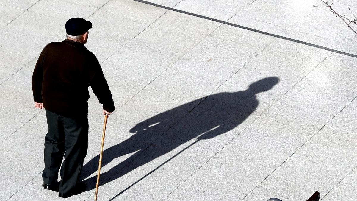 Un anciano camina por la calle apoyándose en un bastón, en una imagen de archivo.