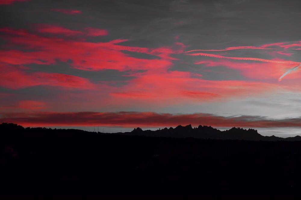 Navarcles. La silueta del paisatge queda retallada pels raigs del sol, que acoloreixen els núvols d'un vermell intens.