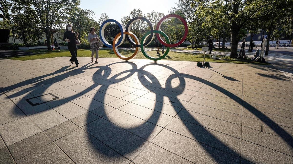 Varias personas caminan junto al monumento de los anillos olímpicos cerca del Estadio Olímpico de Tokio.