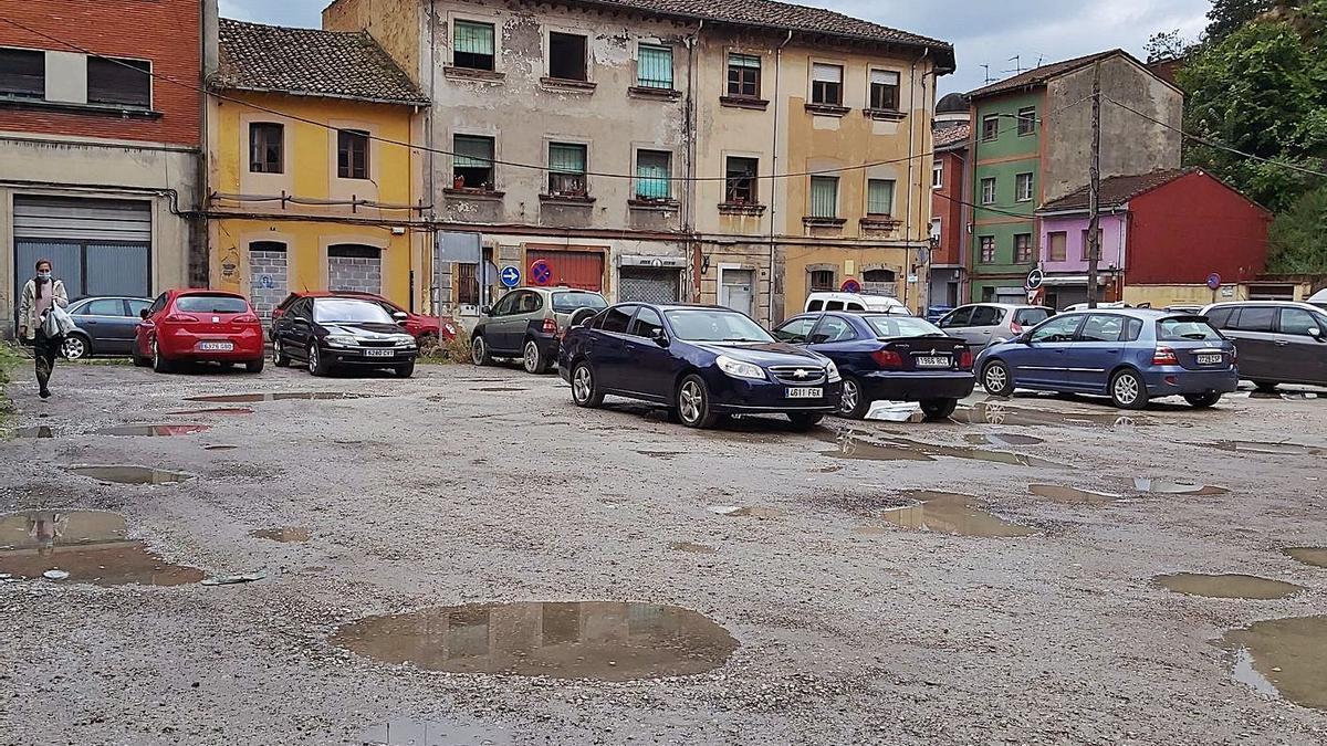 El solar donde se construirá el Palacio de Justicia, con los vehículos aparcados frente a los edificios en estado de ruina de la calle Alonso Nart, que serán derribados para habilitar los nuevos estacionamientos. | E. P.