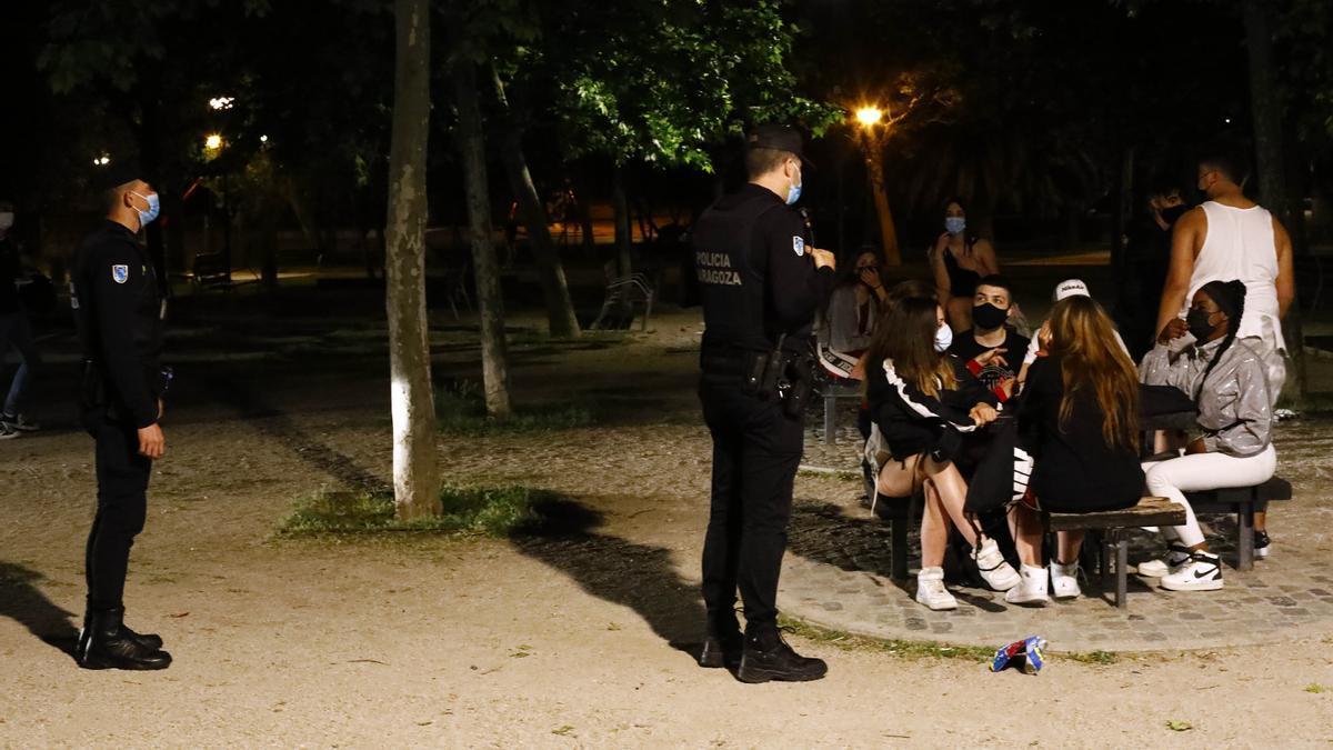 Varios policías inspeccionan a un grupo de jóvenes.