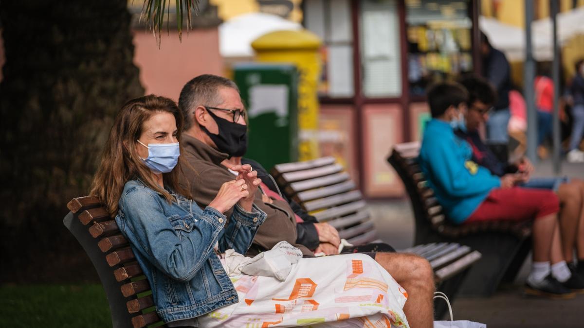 Una pareja con mascarilla descansa en un banco.