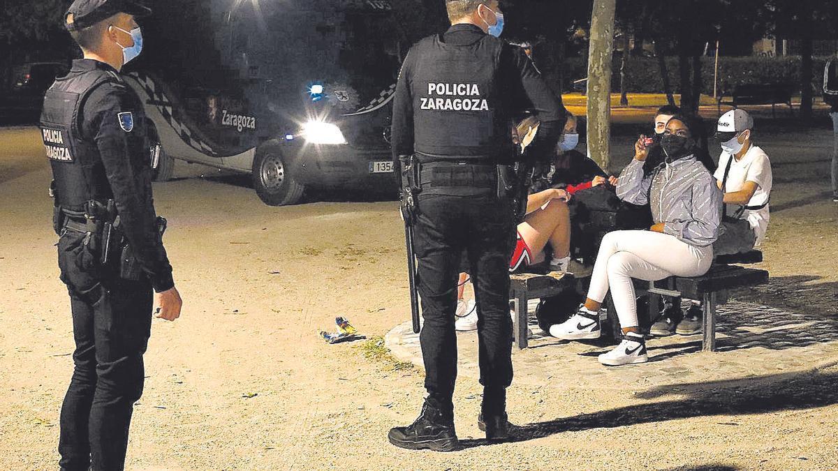 Dos agentes de la UAPO de la Policía Local de Zaragoza durante el dispositivo especial del covid en un parque