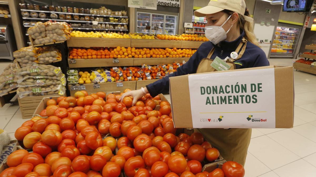 Trabajadora de HiperDino selecciona tomates para donar
