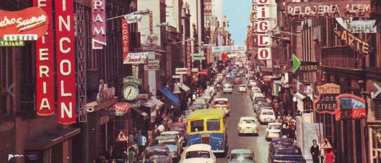 La calle mayor de Triana, repleta de coches y negocios, durante la década de los 60.