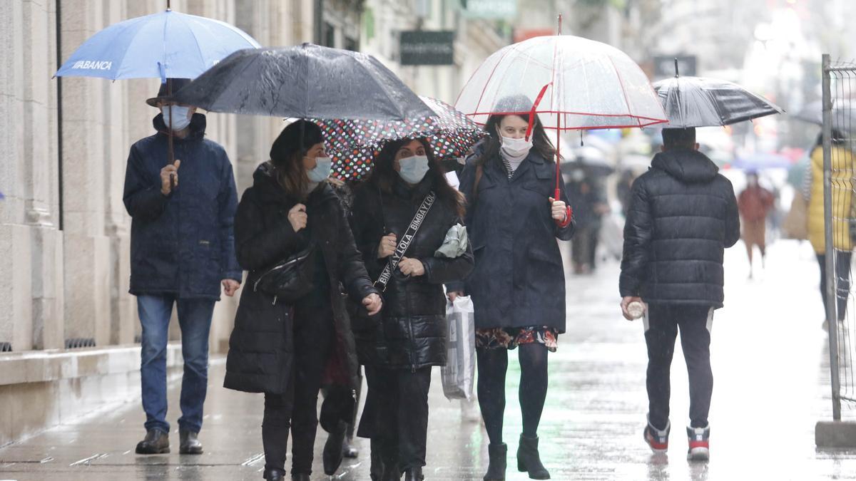 Un grupo de mujeres se protegen de la lluvia, ayer en Vigo