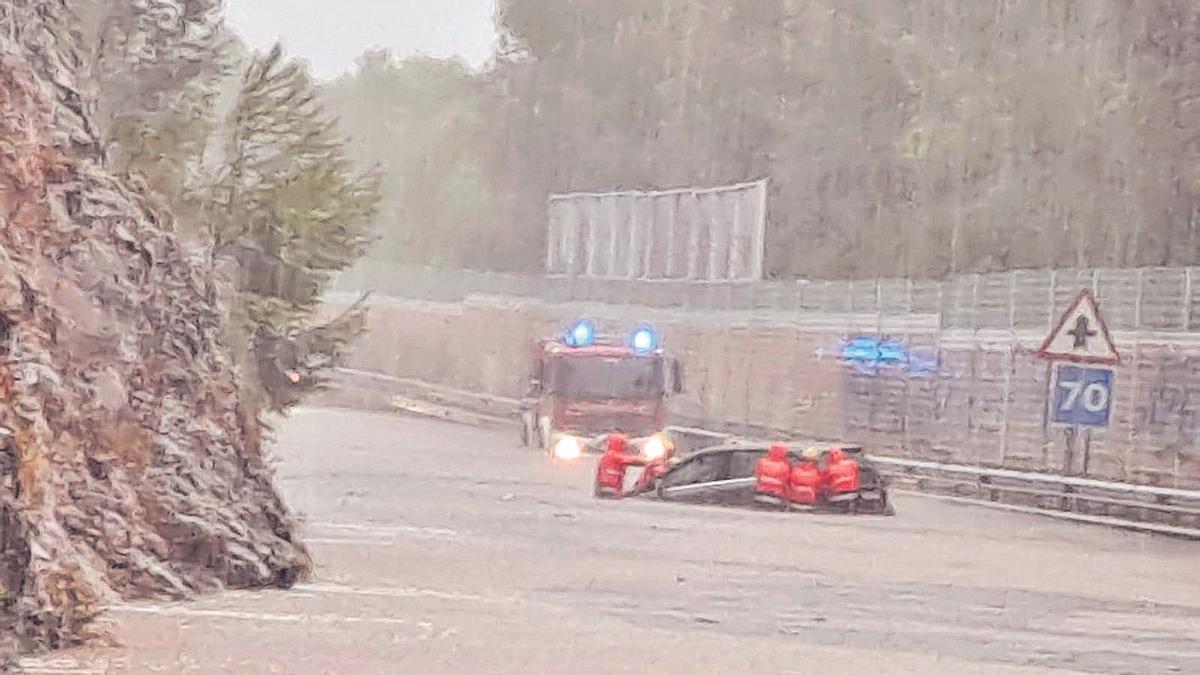 Efectivos de emergencias, junto a un coche atrapado bajo el agua en Alcúdia.