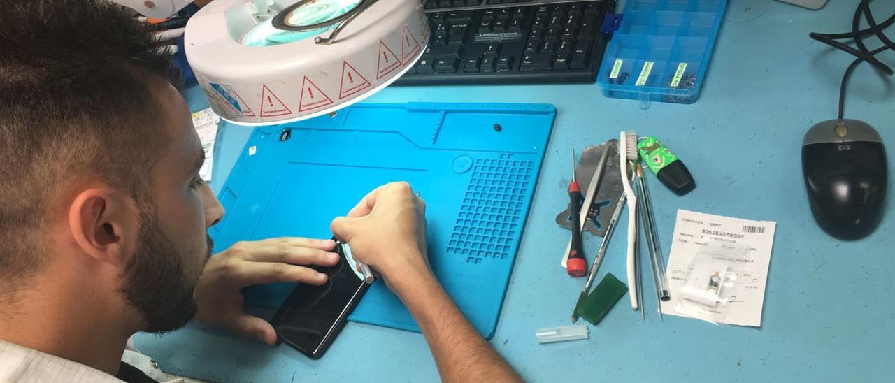 Un operario de Smaaart repara un teléfono móvil.