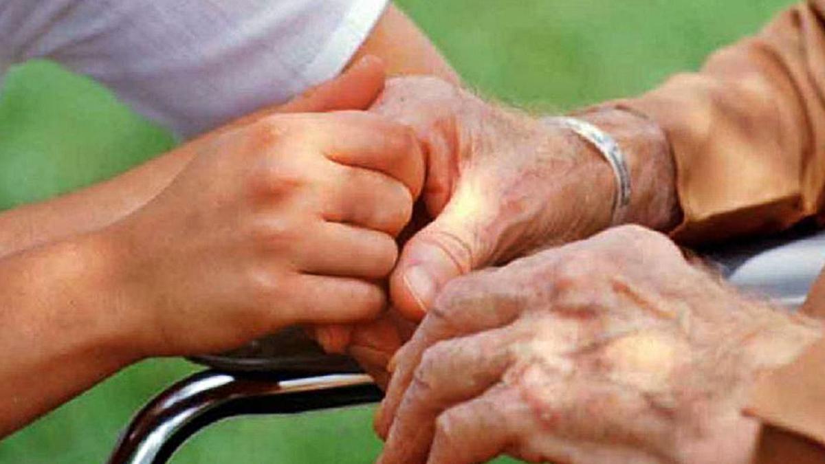 Una cuidadora acoge la mano de un persona mayor. | Agencias