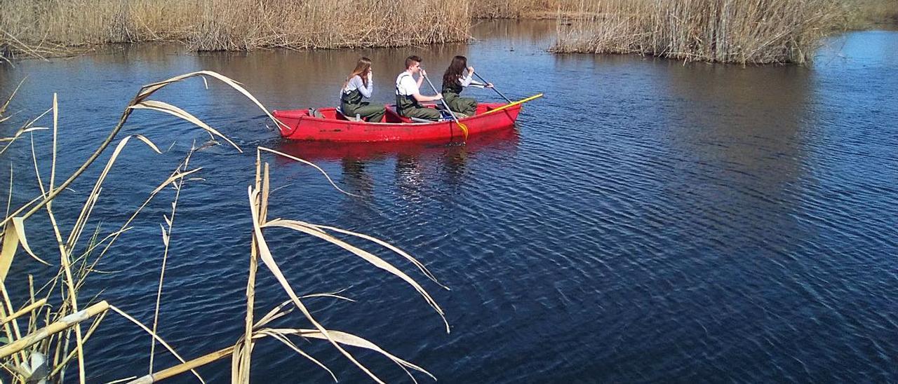 Tres jóvenes en una barca navegando por uno de los «lluents» del Marjal de Pego-Oliva. | LEVANTE-EMV