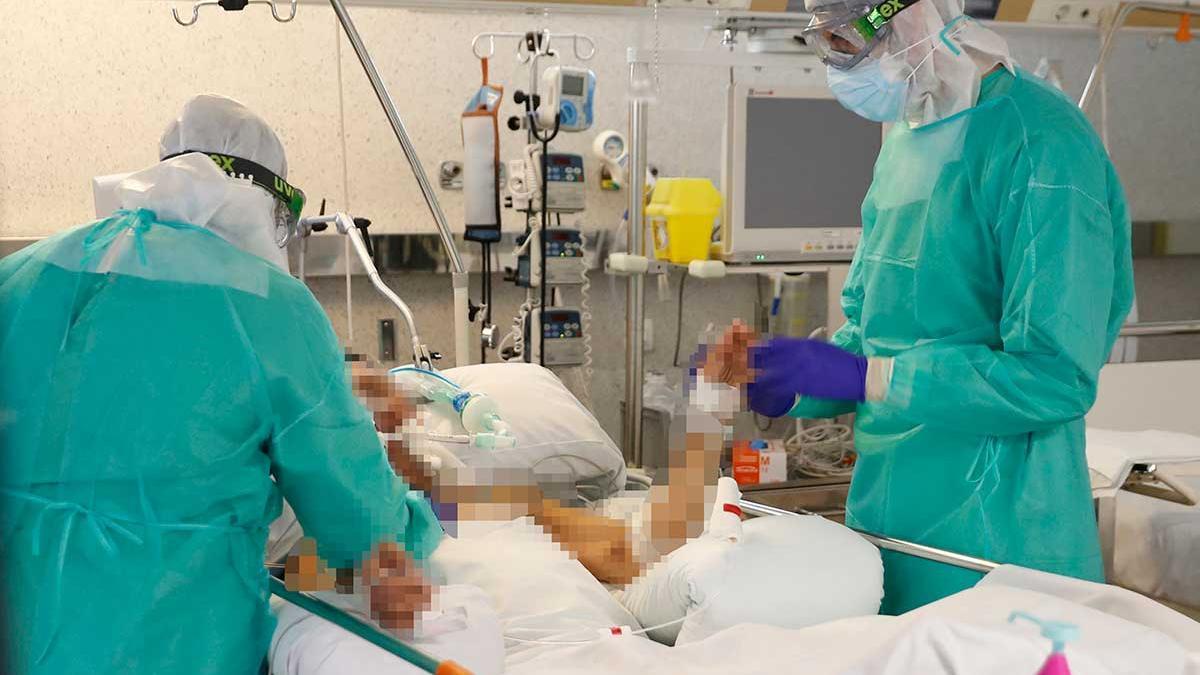 Dos sanitarios de Povisa atienden a un enfermo de Covid-19 en la UCI.