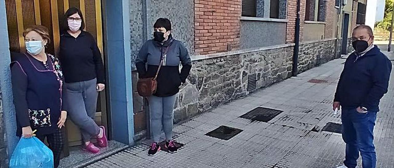 el vecindario. A la izquierda, Enrique Benito conversa junto a un portal del barrio con Avelina Madera, Nuria Pérez y Sandra Fernández. En el centro, Javier Suárez, durante el recreo en el colegio. A la derecha, María Luisa Iglesias, en su tienda de Figaredo.  | D. M.