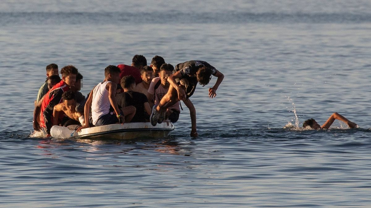 Varios menores migrantes se lanzan al agua para alcanzar la playa ceutí de El Tarajal mientras intentan llegar a España a bordo de una barca.