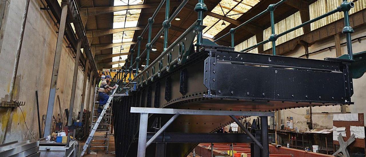 Dos operarios trabajando en el puente giratorio de Ondarroa que se está restaurando en la empresa carreñense. | Borja García