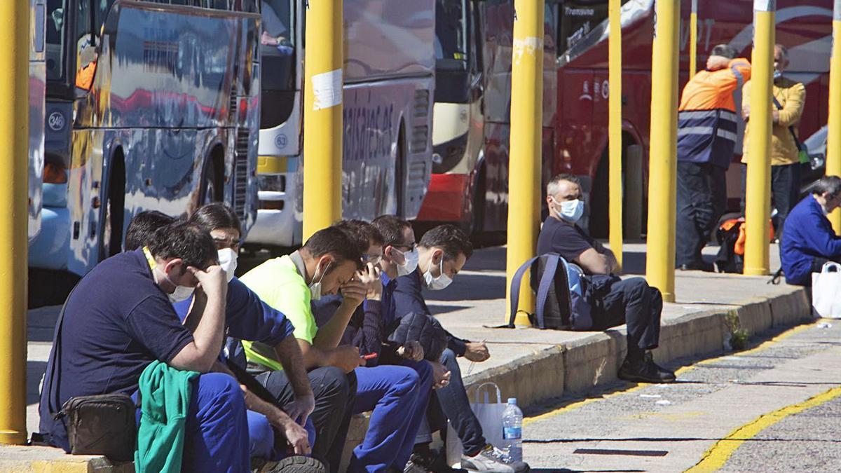 Trabajadores de Ford aguardan en la lanzadera de buses de la planta tras finalizar su turno.   PERALES IBORRA