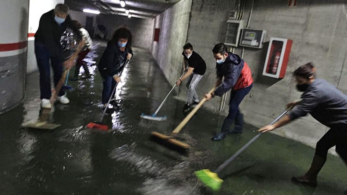 Los vecinos del edificio de la Avenida de Redondela limpian el agua acumulada en el garaje. |   // FDV