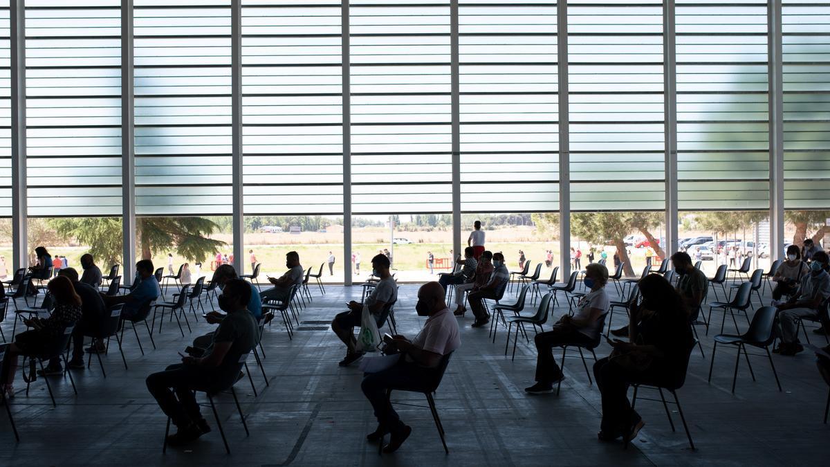 Ciudadanos recién vacunados esperan el tiempo prudencial, mientras otros esperan fuera del recinto de Ifeza