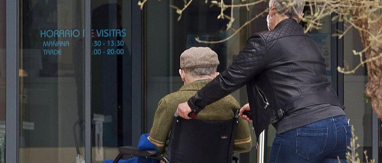 Una mujer pasea a un anciano en una silla de ruedas. | |