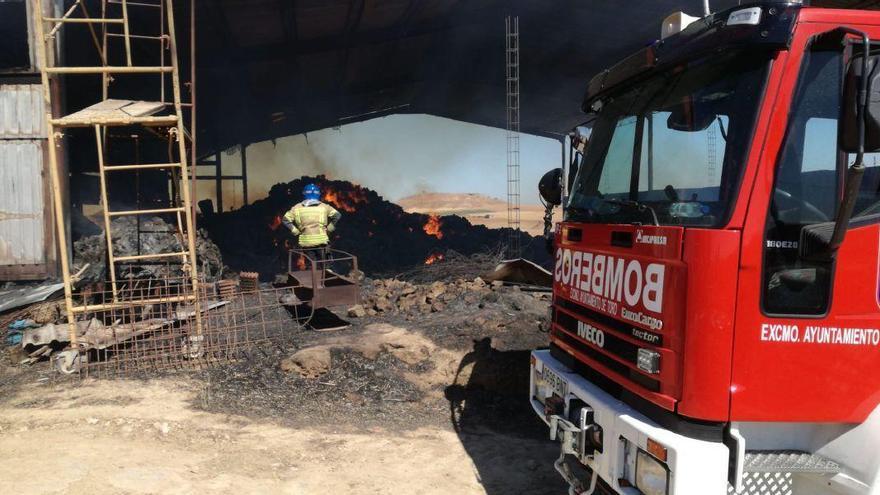 Los bomberos refrescando la navce afectada para evitar reproducciones
