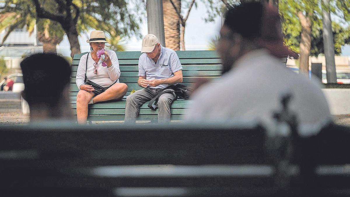 Vecinos descansan en unos bancos del centro de Santa Cruz.