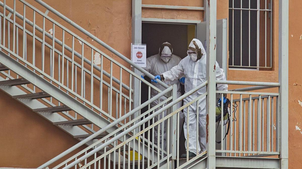 Dos trabajadores salen de la residencia por la escalera trasera con equipos de protección. | PERALES IBORRA