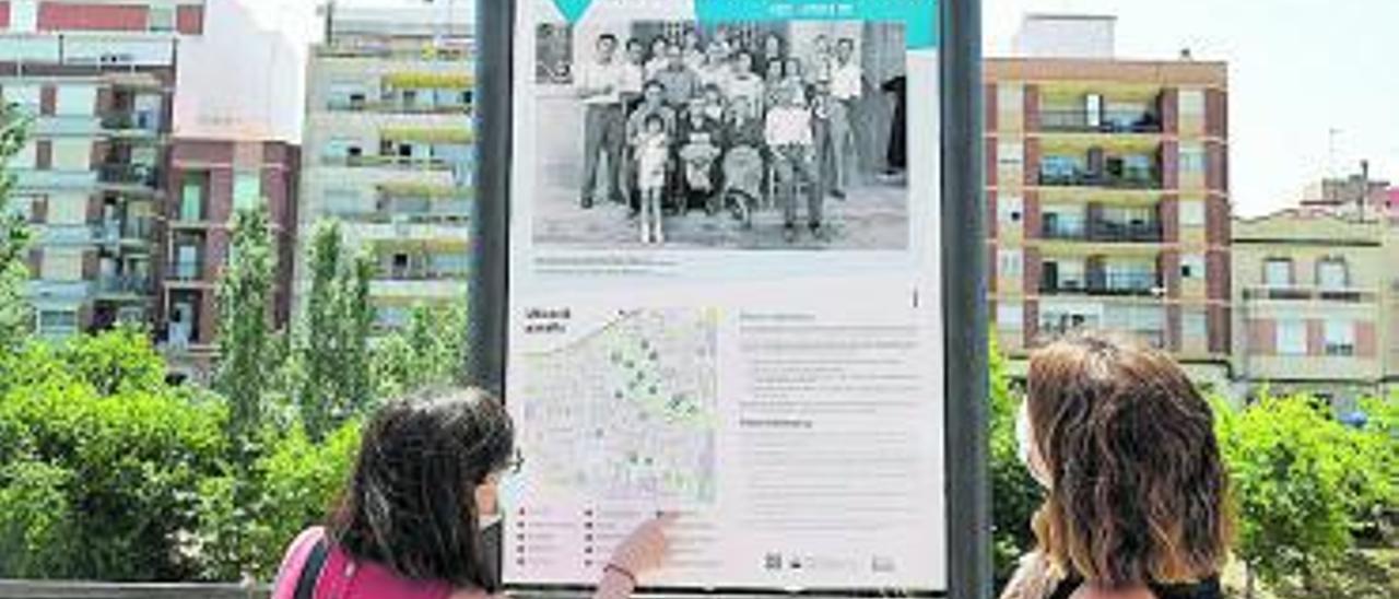 Unes veïnes observen uns dels panells de la mostra. | A. P.