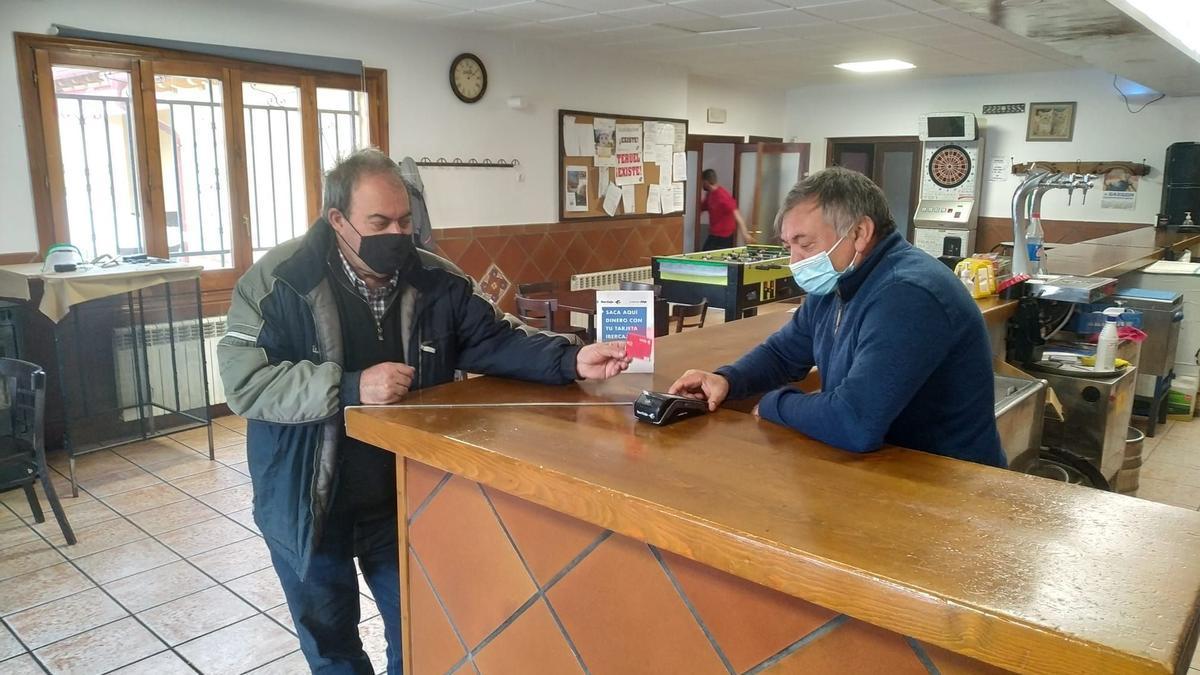 Un cliente saca dinero con su tarjeta de Ibercaja en el mostrador del bar El Gato de Guadalaviar, regentado por Santiago