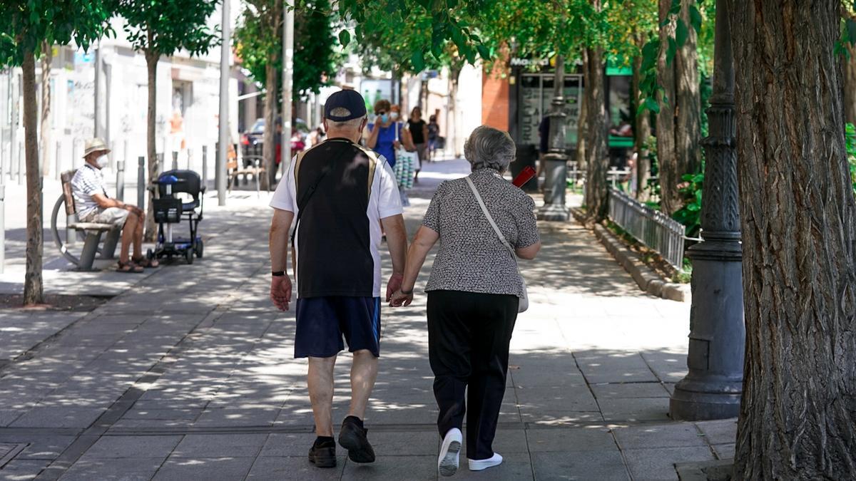 Una pareja de ancianos caminando por la calle cogidos de la mano.