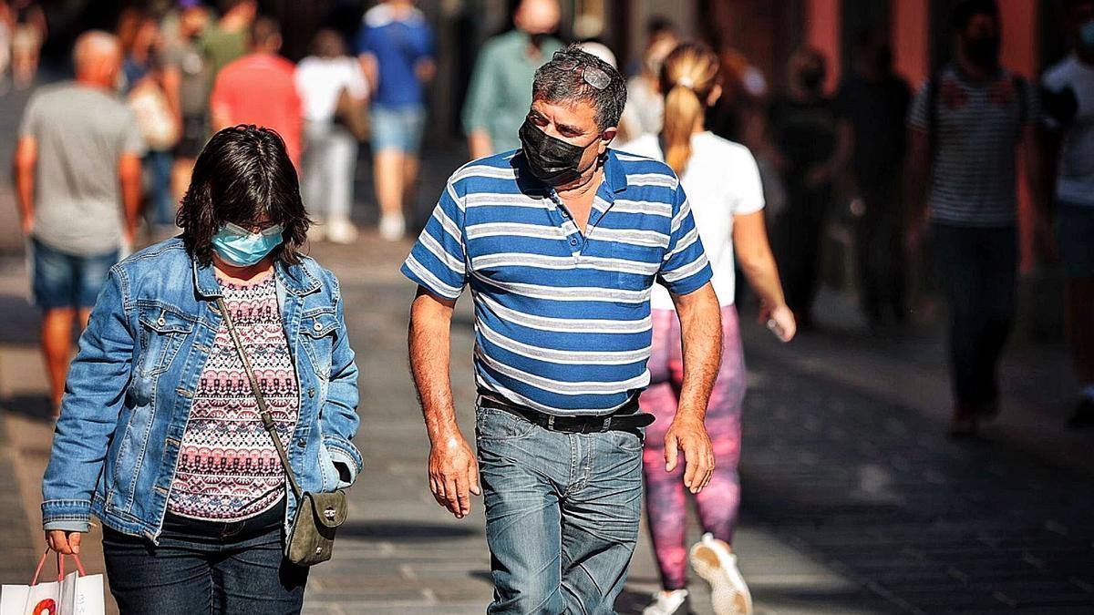 Varias personas pasean con mascarilla para evitar contagios por Covid en el centro de Santa Cruz de Tenerife.