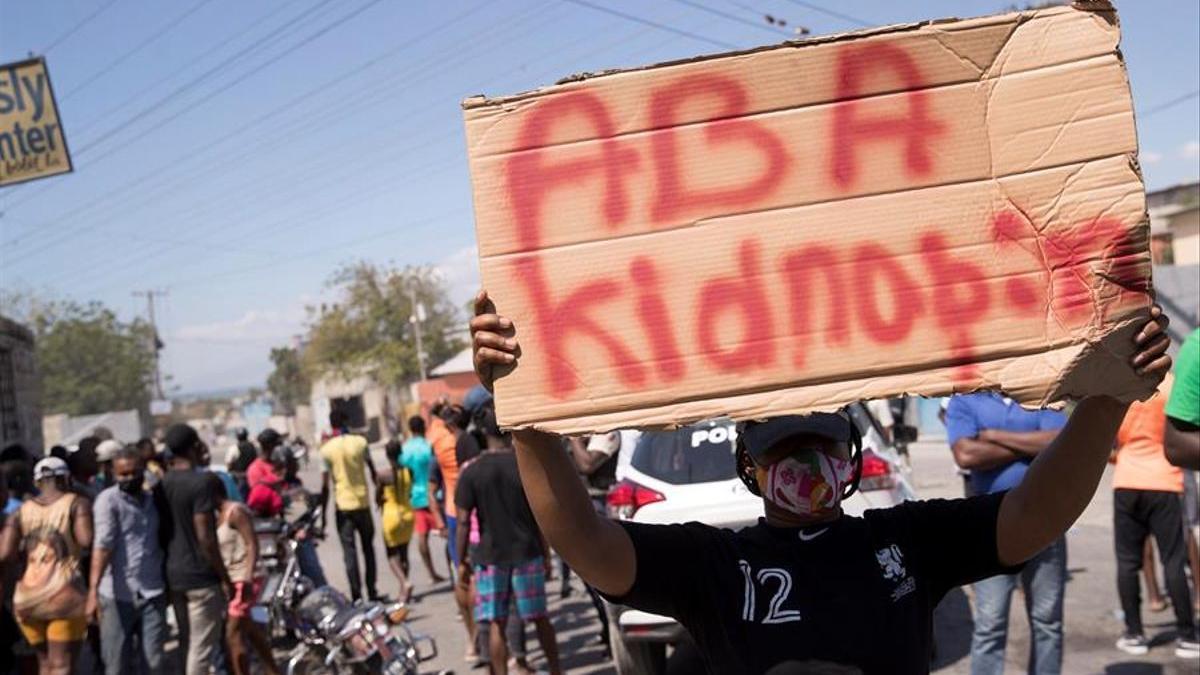 """Un grupo de manifestantes grita arengas y carga letreros con la frase """"Abajo los secuestros"""" en Haití."""