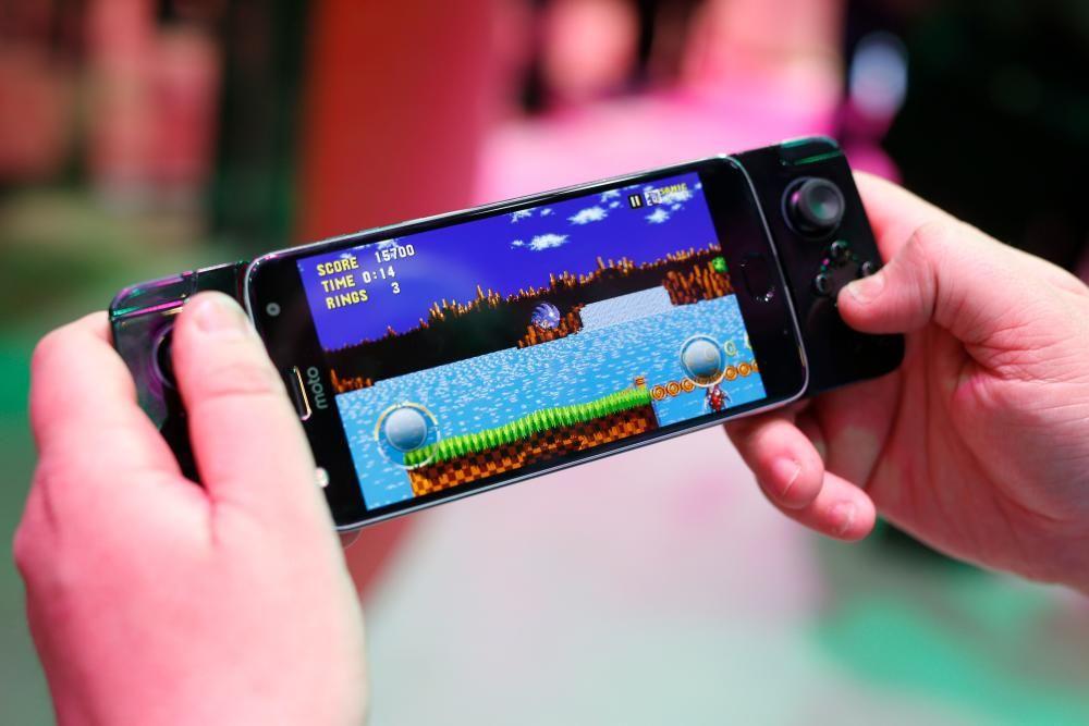 Un hombre juega a un videojuego con un gamepad en el Motorola Moto Z.