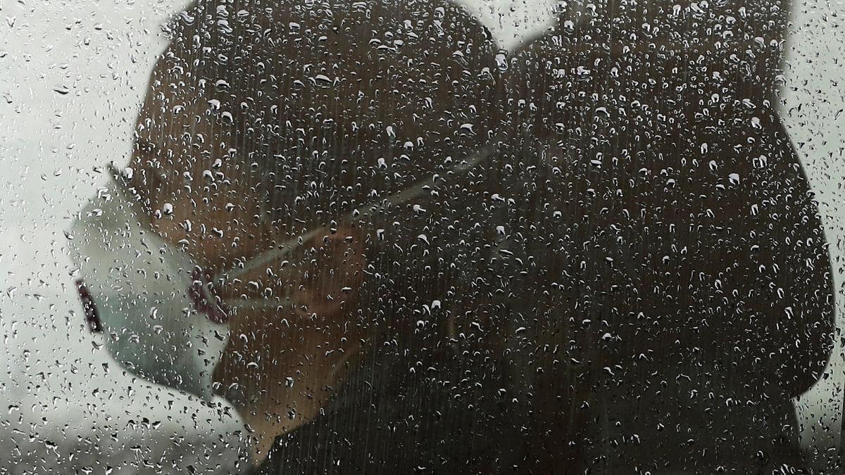 Una persona en el interior de su vehículo con mascarilla.