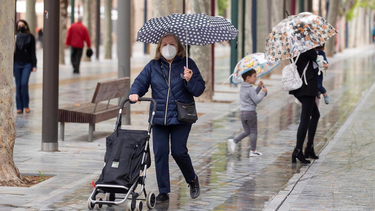 Varias personas se resguardan de la lluvia bajo paraguas
